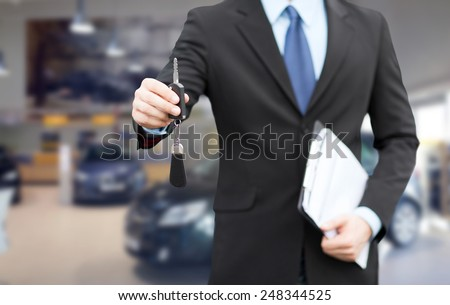 auto business, car sale, gesture and people concept - close up of businessman or salesman with documents giving car key over auto show background - stock photo