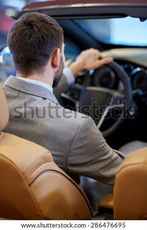 auto business, car sale, lifestyle and people concept - close up of man sitting in cabriolet car at auto show or salon - stock photo