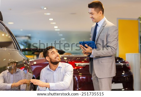 auto business, car sale, technology and people concept - happy man and car dealer with tablet pc computer talking in auto show or salon - stock photo