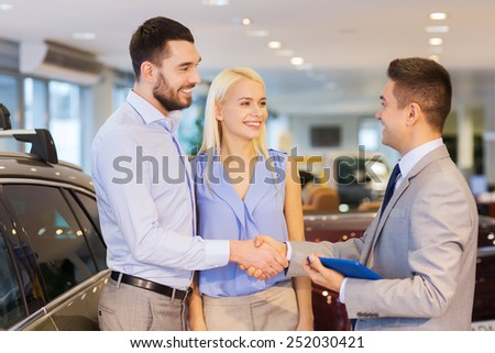 auto business, car sale, technology, gesture and people concept - happy couple with car dealer shaking hands in auto show or salon - stock photo
