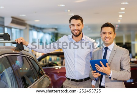 auto business, car sale, techology and people concept - happy man and car dealer with tablet pc computer in auto show or salon - stock photo