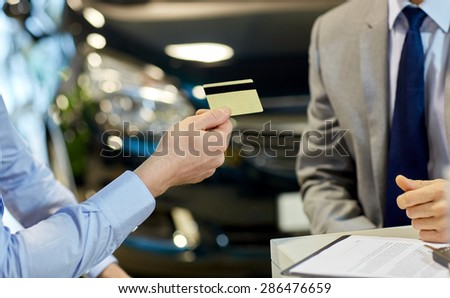 auto business, sale and people concept - close up of customer giving credit card to car dealer in auto show or salon - stock photo