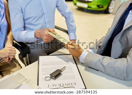 auto business, sale and people concept - close up of customers giving money to dealer and buying car in auto show or salon - stock photo