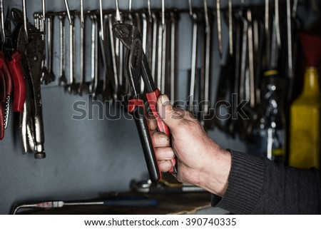 auto car mechanic taking wrench  and pliers working tools  tools  in automobile at repair service. Garage concept