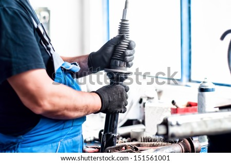 Auto car mechanic working on car shock absorber in car service workshop