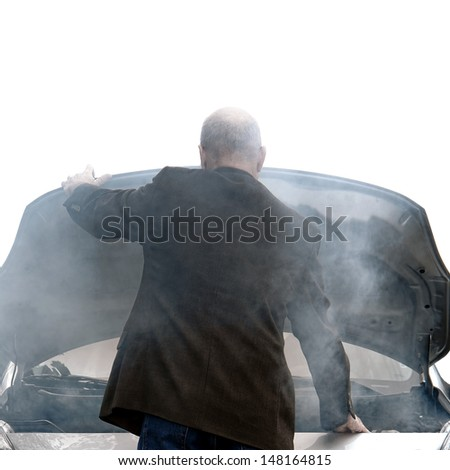 Auto driver standing in front of a broken down car open engine compartment hood with smoke from an automotive fire or hose leak steam waiting for emergency repair on a road - stock photo