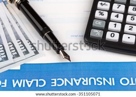 auto insurance claim form with fountain pen and dollar