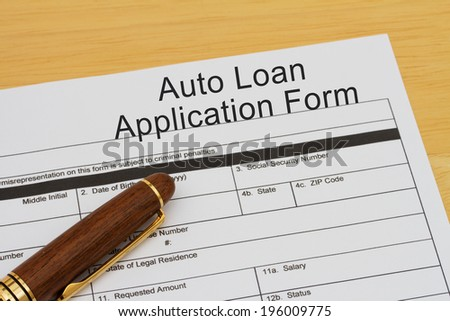 Auto Loan Application Form with a pen on a wooden desk