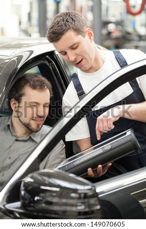 Auto mechanic and car owner. Confident auto mechanic explaining something to a customer sitting at the front seat of car