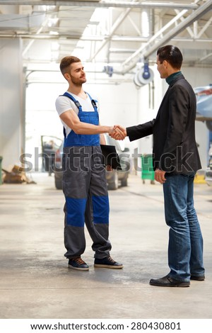 Auto Mechanic And Customer in Auto Repair Shop - stock photo