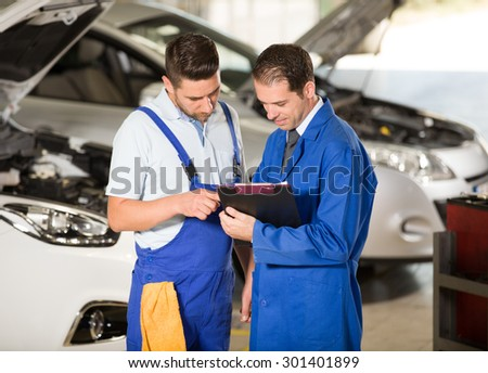 Auto mechanic and manager working in repair shop. - stock photo