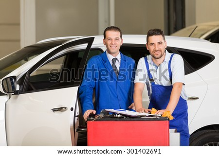 Auto mechanic and technician posing at camera in repair shop. - stock photo