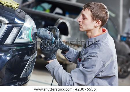 auto mechanic buffing and polishing car headlight  - stock photo
