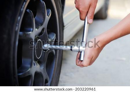 Auto mechanic changing car wheel - stock photo