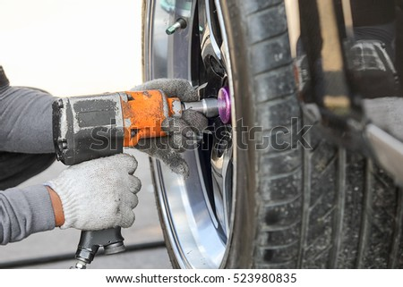 Auto mechanic changing racing car wheel