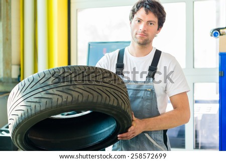 Auto mechanic changing tire in car workshop - stock photo