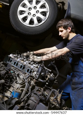 Auto mechanic checking an internal combustion engine - stock photo
