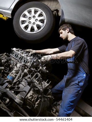 Auto mechanic checking an internal combustion engine. - stock photo