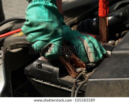 Auto mechanic checking car battery in gloves - stock photo