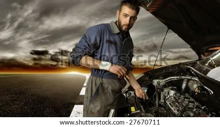 Auto mechanic checking car on the street - stock photo