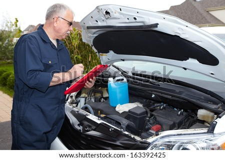 Auto mechanic checking engine. Car repair service. - stock photo
