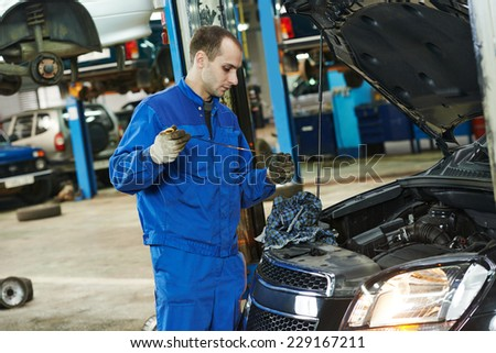 Auto mechanic checking oil level in car engine at garage service station - stock photo