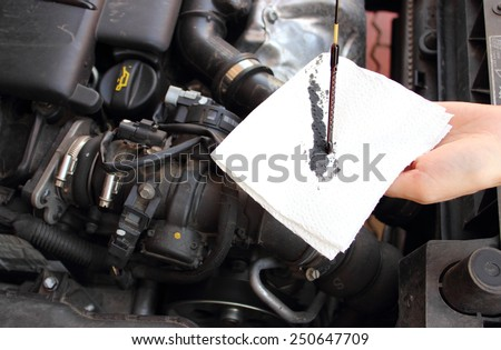 Auto mechanic checks the oil level in a car engine - stock photo