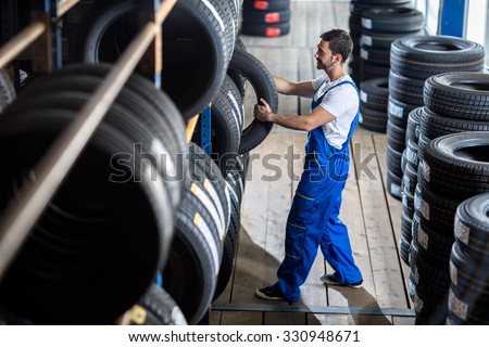 Auto mechanic  choose tire for car at a tire store - stock photo