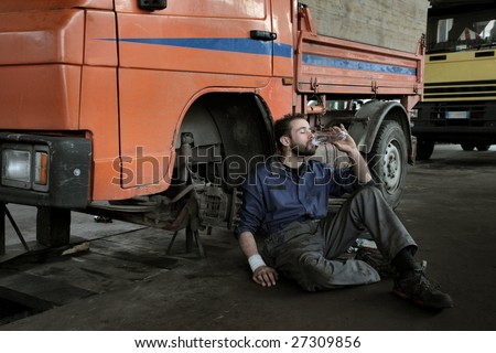 auto mechanic drinking a bottle of water - stock photo