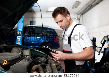 Auto mechanic examining car - stock photo