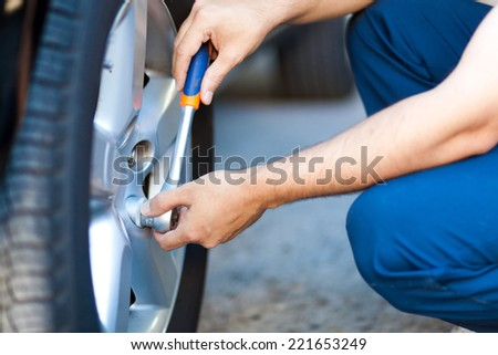 Auto mechanic in his workshop changing tires or rims - stock photo