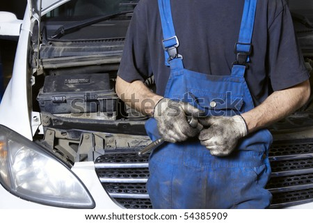 Auto mechanic in uniform holding work tool - stock photo
