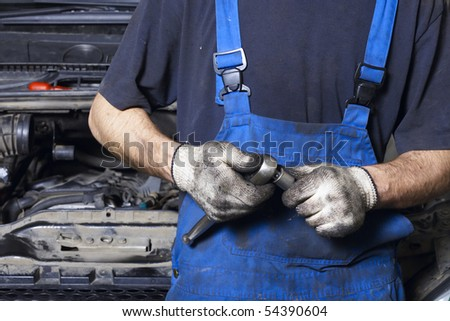 Auto mechanic in uniform holding work tool - stock photo