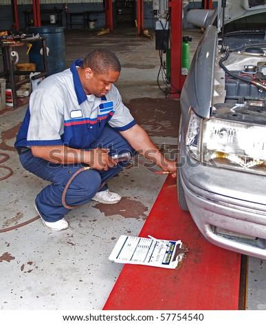 Auto mechanic inspecting a carâ??s tire pressure in a service garage. - stock photo