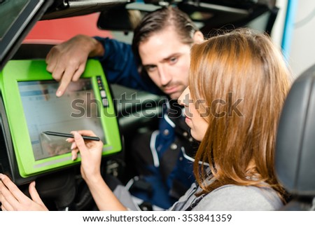 Auto mechanic is guiding a female trainee in checking the car performance with a digital device. Concept for the fact that more and more women participate in jobs previously typical for men.  - stock photo