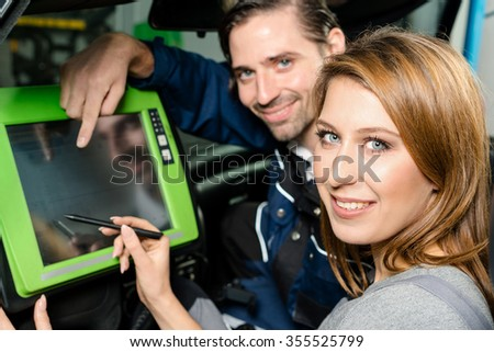 Auto mechanic is guiding an attractive female trainee in checking the car performance with a digital device. Concept for the fact that more and more women participate in jobs previously typical for - stock photo