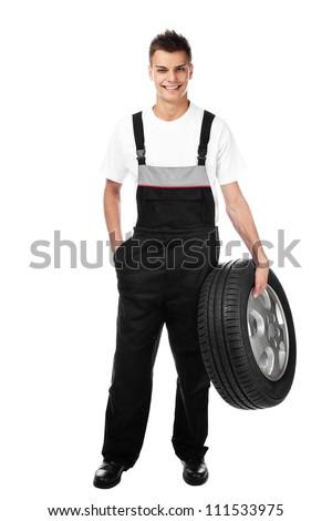 Auto mechanic isolated holding car wheel smiling - stock photo