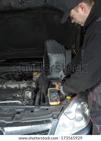 Auto mechanic measuring car battery voltage using multimeter - stock photo