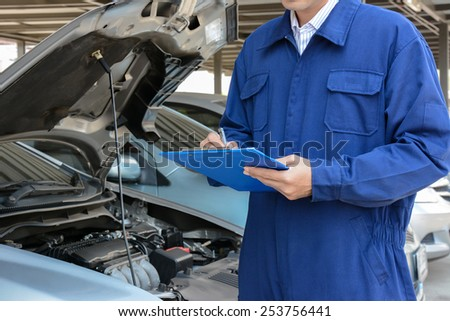 Auto mechanic (or technician) checking car engine at the garage - soft focus - stock photo