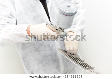 auto mechanic  painting car parts in a special booth  against white background