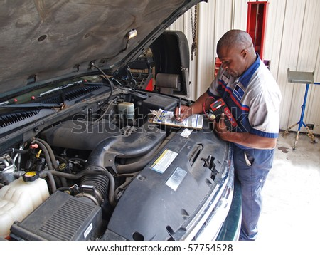 Auto mechanic performing a routine service inspection in a service garage. - stock photo