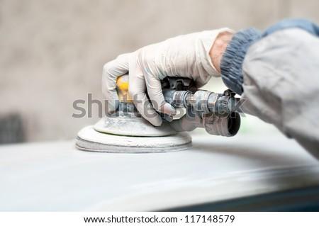 Auto mechanic polishing the car for painting - stock photo