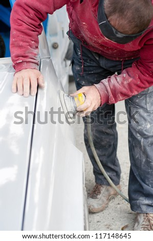 Auto mechanic preparing the car for paint job by applying polish with the power buffer machine