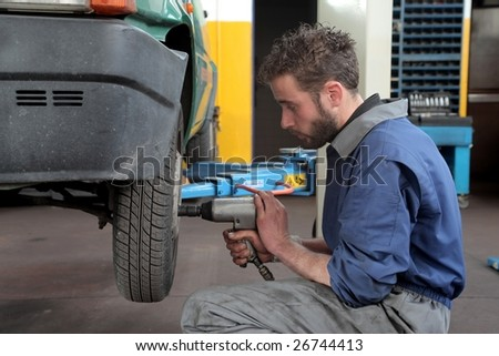 Auto mechanic removing wheel of a car in a workshop - stock photo