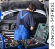 auto mechanic repairing a car engine. Different work tools on foreground. - stock photo