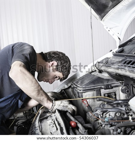 auto mechanic repairing a car engine. Space for text. - stock photo
