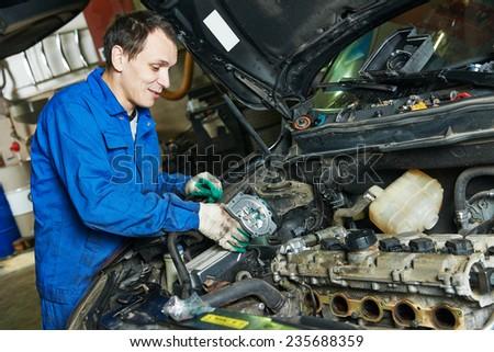auto mechanic repairing automobile car engine turbine at maintenance repair service station garage - stock photo
