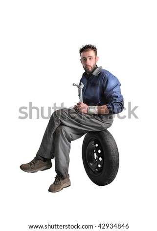 auto mechanic seated on a wheel and holding a wrench - stock photo