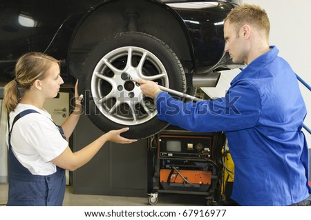 Auto mechanic shows the female trainee changing the wheels of a car in workshop in front of a car - stock photo