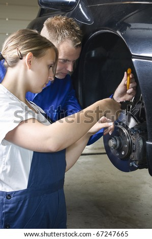 Auto mechanic shows the female trainee maintenance of the brakes in workshop in front of a car - stock photo